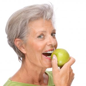 woman smiling preparing to eat apple