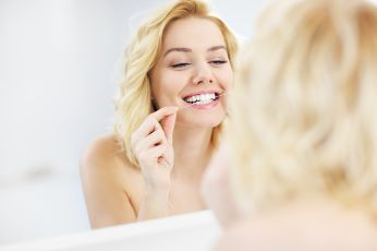 Woman flossing in the mirror