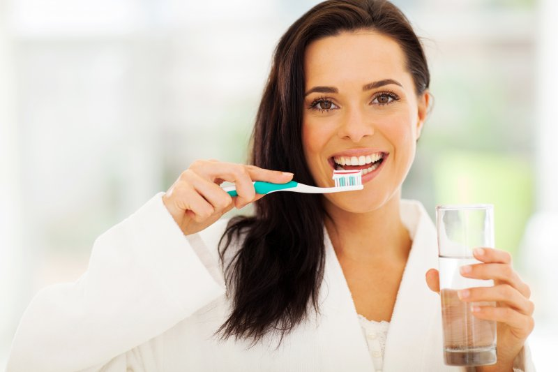 Woman smiling and brushing her teeth