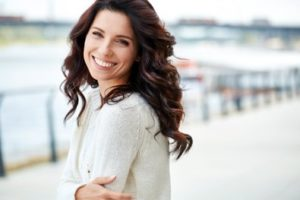 Woman with brown hair wearing a white sweater smiling