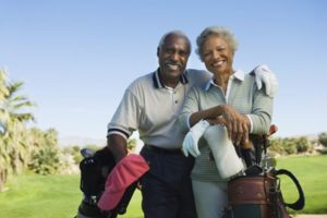 Senior couple smiling on a golf course