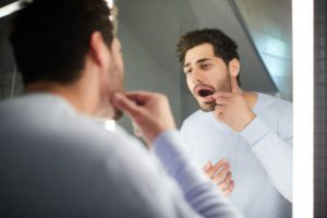 man looking at his dental crown in the mirror