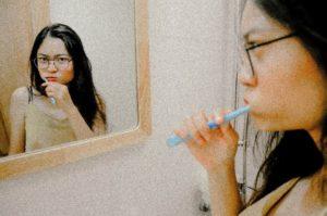 Woman brushing her teeth at dentist in Upper Arlington